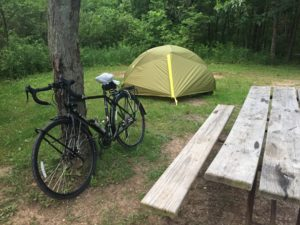 Foreground: an empty picnic table, a black touring bike with a plastic bag around the saddle leaning on a tree. Behind them is a green tent with bushes behind that.