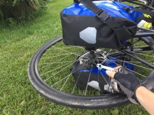 The front wheel of a bike with panniers still attached to the rack. A hand is holding up a spoke tool in front of the wheel.
