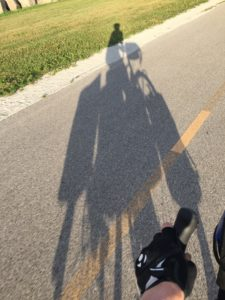 A shadow silhouette of loaded bike and rider.