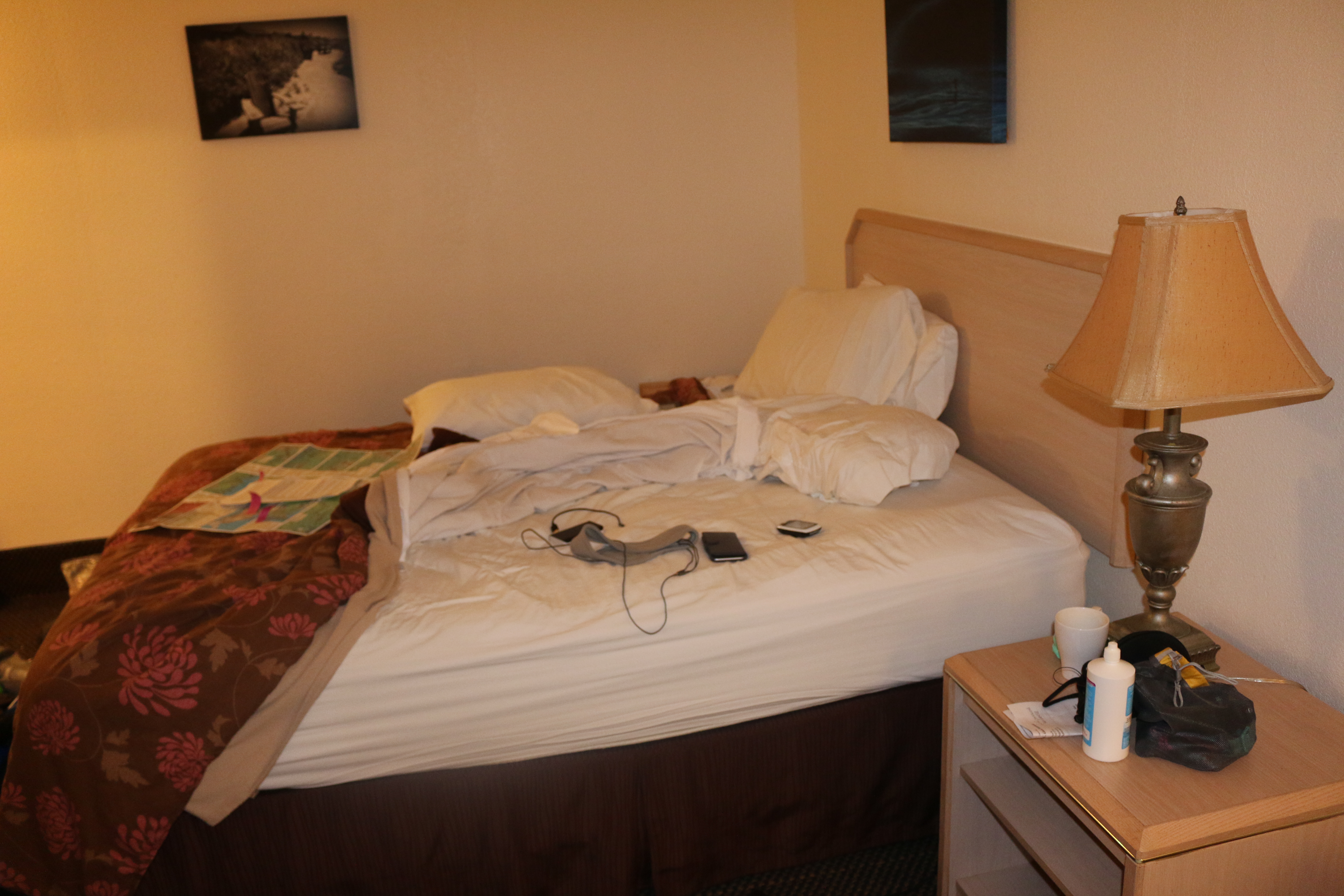 A hotel room bed, unmade and cluttered.
