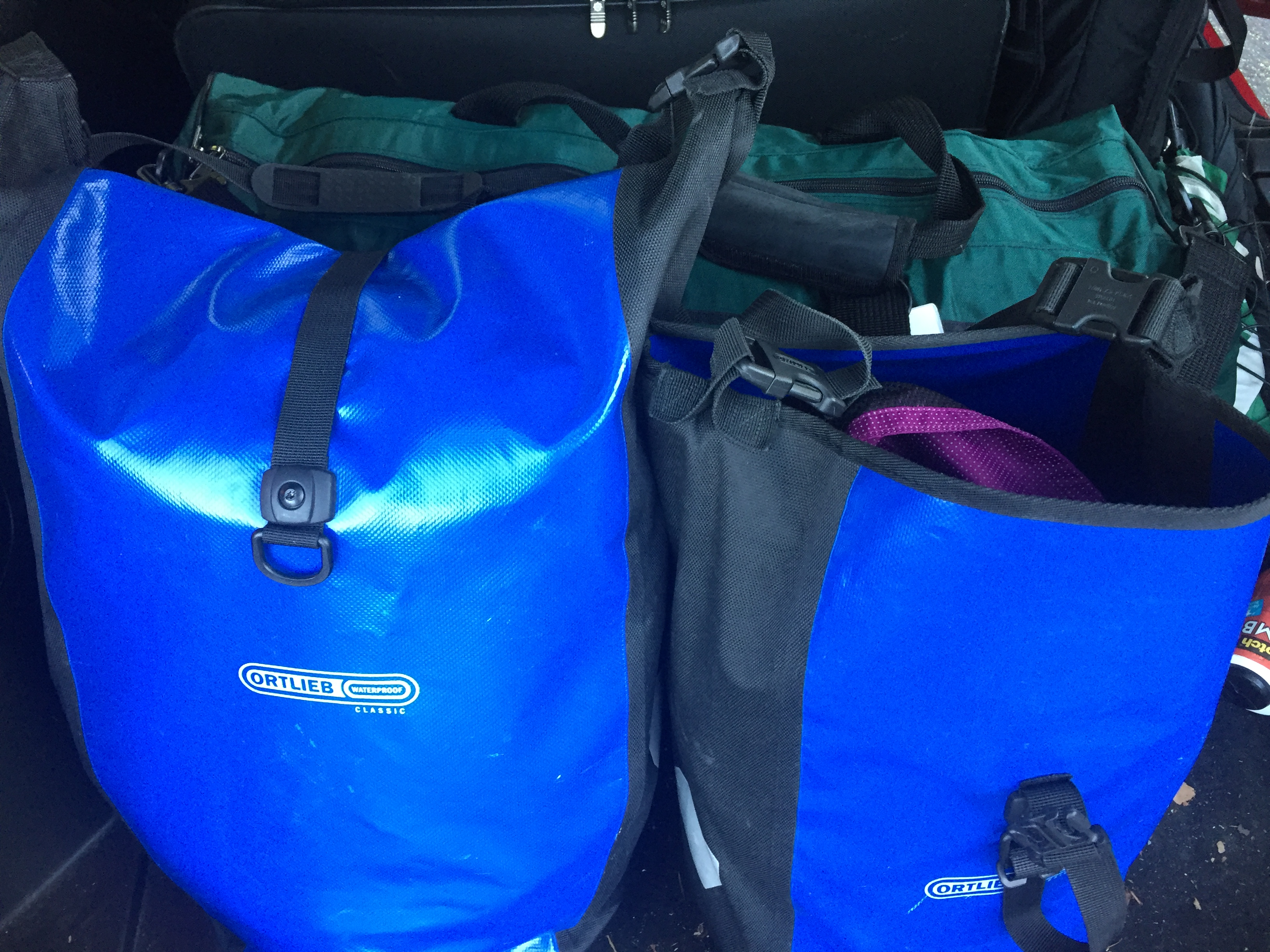 A long, green duffel bag with two blue ortlieb panniers in the foreground.
